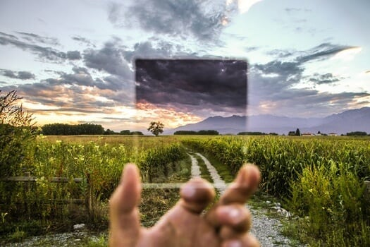 Focusing glass over a trail through green field